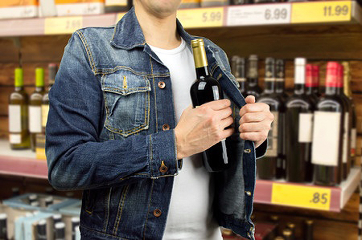 35823122 - man in a supermarket stealing a bottle of champagne